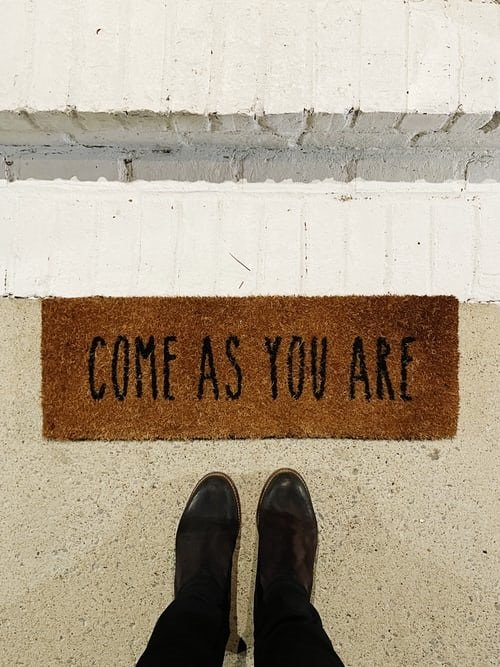 """looking down at door mat with words, """"Come as you are"""""""